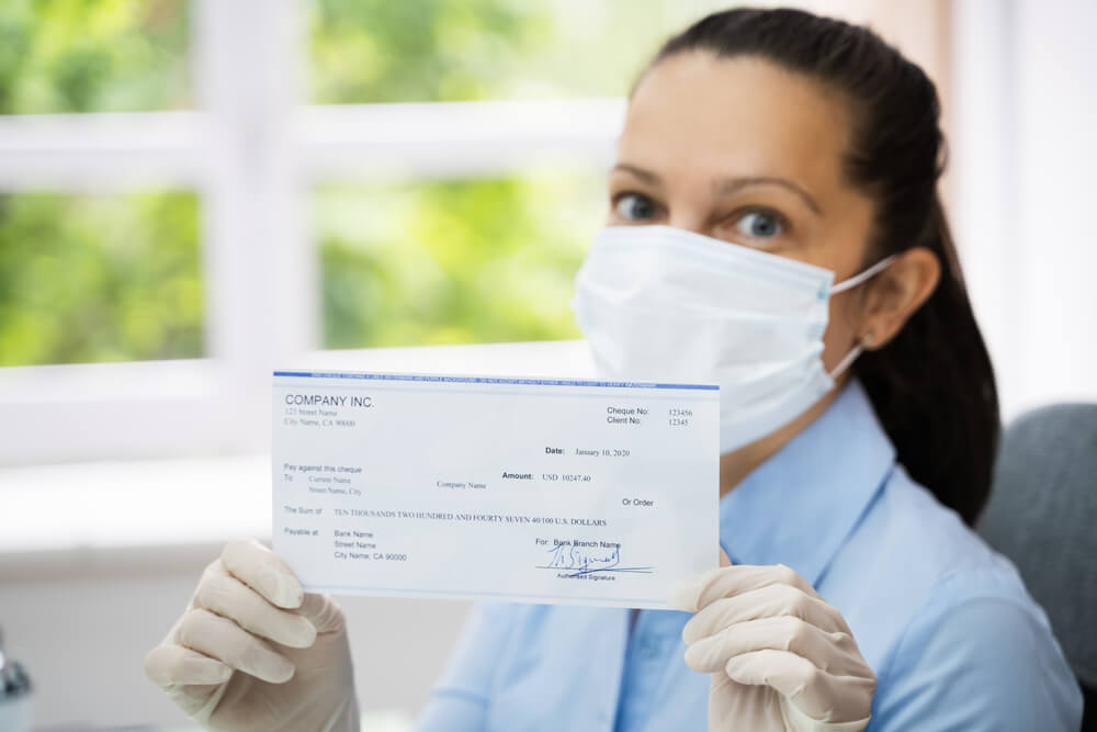 woman wearing a mask holding a stimulus check