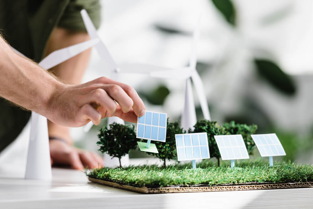 a woman's hand holding a mini solar panel from a solar farm model