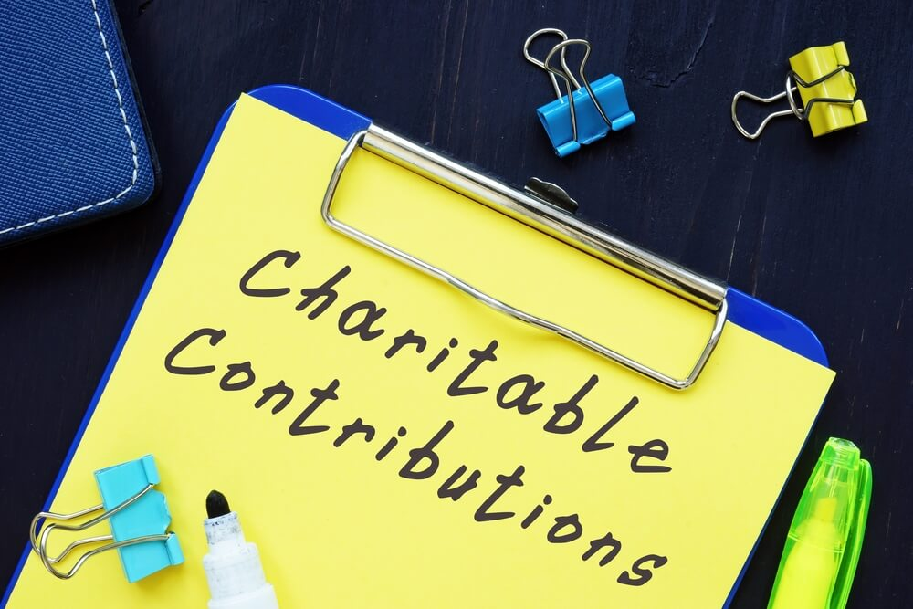 Charitable Contributions written on yellow paper on clipboard
